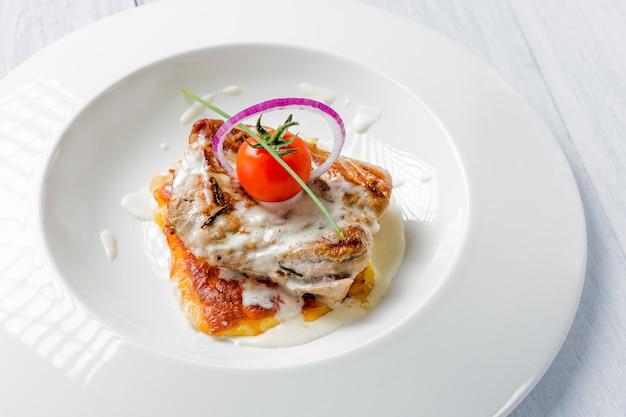 Smaczne kawałki pieczonej wieprzowiny z sosem serowym, pomidorem i cebulą na białym talerzu z bliska
