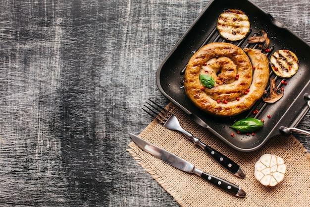 Smaczne kiełbaski ślimak udekorować czerwonym pieprzem i bazylią