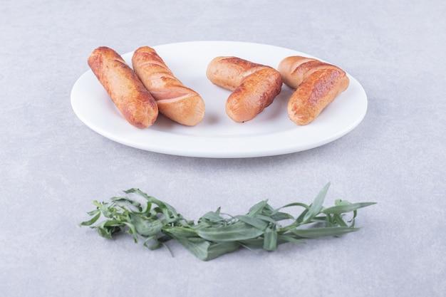 Smaczne kiełbaski z grilla na białym talerzu.