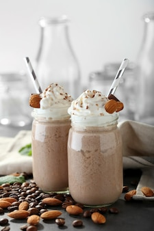 Smaczne koktajle mleczne z ziarnami kawy i orzechami migdałowymi na stole
