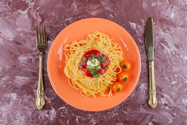 Smaczne, kolorowe, apetyczne gotowane spaghetti z sosem pomidorowym i świeżymi żółtymi pomidorkami cherry.