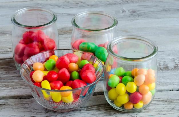 Smaczne kolorowe cukierki w szklanej misce i słoikach