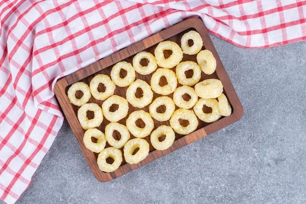 Smaczne krakersy w kształcie koła na drewnianym talerzu z obrusem