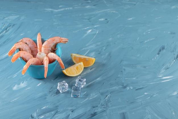 Smaczne krewetki w misce obok cytryn i kostki lodu, na marmurowym tle.