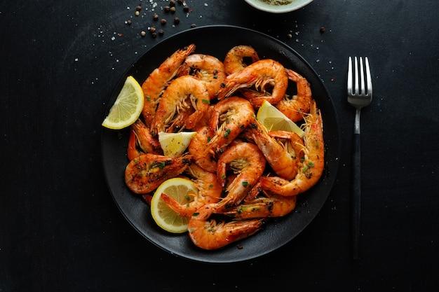 Smaczne krewetki z przyprawami i sosem na talerzu na ciemnej powierzchni