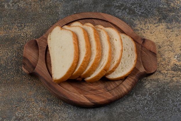 Smaczne kromki białego chleba na desce