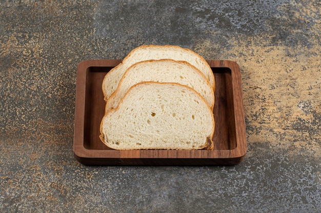Smaczne kromki białego chleba na drewnianym talerzu