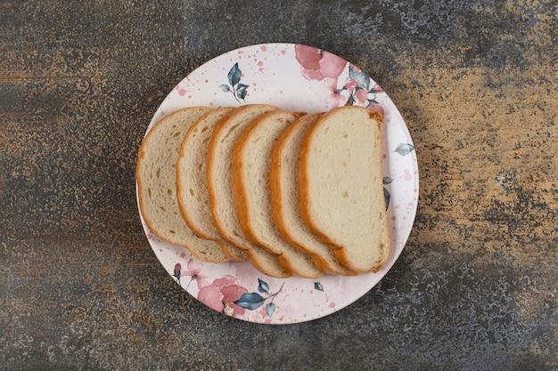 Smaczne kromki białego chleba na kolorowym talerzu.