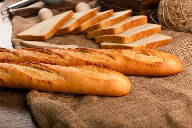 Smaczne kromki chleba z bagietką na obrusie