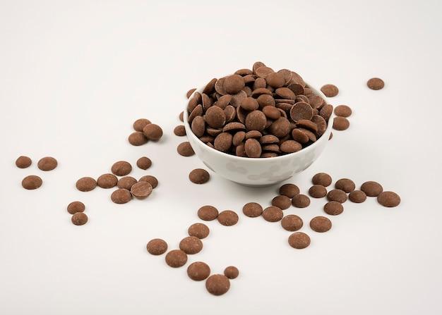 Smaczne krople czekolady mlecznej w misce na białym tle.