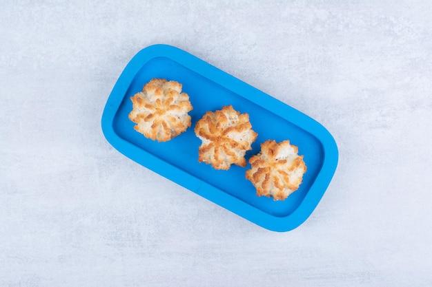 Smaczne makaroniki kokosowe na niebieskim talerzu. zdjęcie wysokiej jakości