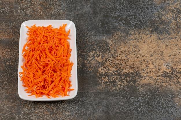 Smaczne marchewki julienned na białym talerzu.