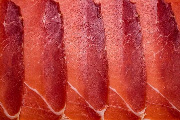 Smaczne mięso w tle, cienko pokrojony jamon.