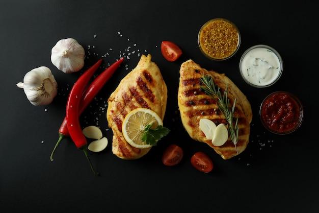 Smaczne mięso z kurczaka z grilla i składniki na czarnym tle, widok z góry