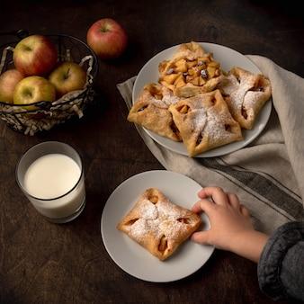 Smaczne mini tarty jabłkowe z cukrem pudrem na ciemnym tle rustykalnym