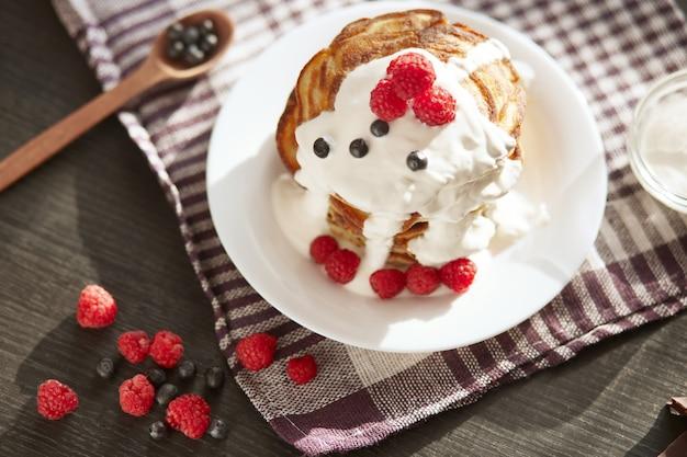 Smaczne naleśniki na bawełnianym ręczniku w kratkę, babeczki z kwaśną śmietaną, świeże jagody i maliny na białym talerzu, łyżka pełna jagód. pyszne naleśniki na śniadanie, koncepcja żywności.