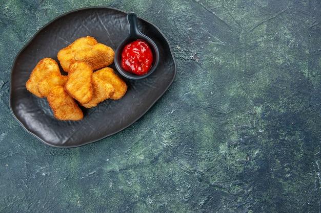 Smaczne nuggetsy z kurczaka i keczup w czarnych talerzach po prawej stronie na ciemnej powierzchni