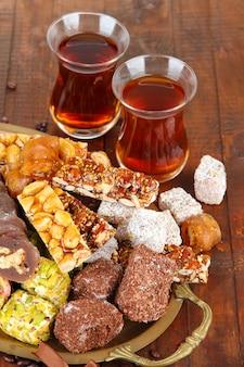 Smaczne orientalne słodycze na tacy i szklanki herbaty, na szarym drewnianym