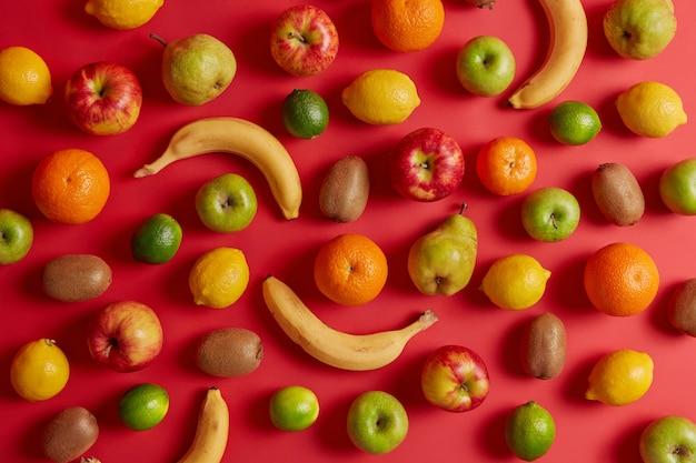Smaczne owoce tropikalne i domowe zebrane z sadu. pyszny apetyczny banan, kiwi, jabłko, gruszka i cytryna na czerwonym tle. asortyment zdrowych, pożytecznych produktów naturalnych. leżał na płasko