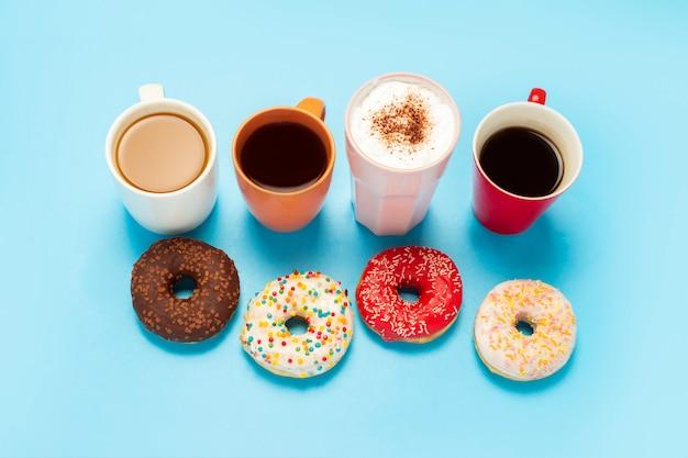 Smaczne pączki i kubki z gorącymi napojami, kawą, cappuccino, herbatą na niebieskiej powierzchni. do
