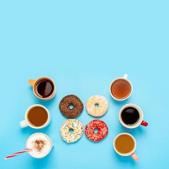 Smaczne pączki i kubki z gorącymi napojami, kawą, cappuccino, herbatą na niebieskiej powierzchni. koncepcja słodyczy, piekarni, ciastek, kawiarni, spotkania, przyjaciół, przyjaznego zespołu. plac. leżał płasko, widok z góry