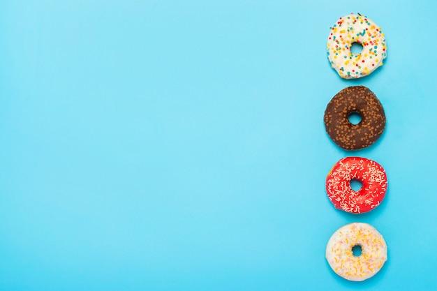 Smaczne pączki różnego rodzaju na niebieskiej powierzchni. pojęcie słodyczy, piekarni, ciastek. . leżał płasko, widok z góry