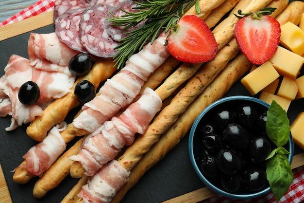 Smaczne paluszki grissini z boczkiem i przekąskami, z bliska