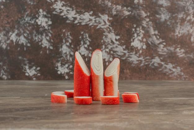 Smaczne paluszki krabowe na marmurowym stole.