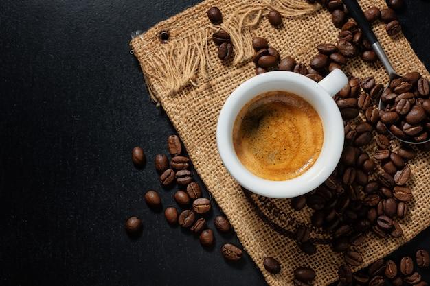 Smaczne parujące espresso w filiżance z ziaren kawy. widok z góry. ciemne tło.
