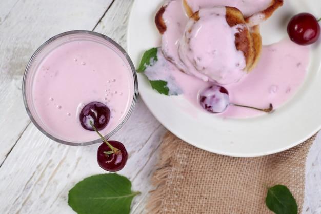 Smaczne, piękne naleśniki na białym talerzu z wiśnią i jogurtem w szklanej filiżance na jasnym drewnianym stole z listkami mięty.