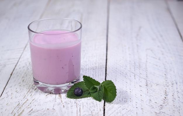 Smaczne, piękne naleśniki z jagodami i jogurtem jagodowym na jasnym drewnianym stole z listkami mięty.