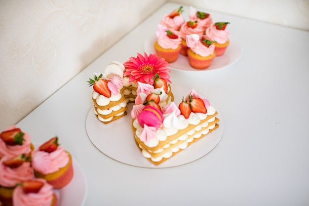 Smaczne, piękne różowe ciasto z truskawkami, piankami, makaronikami i ogromnym kwiatkiem na 2 urodziny.