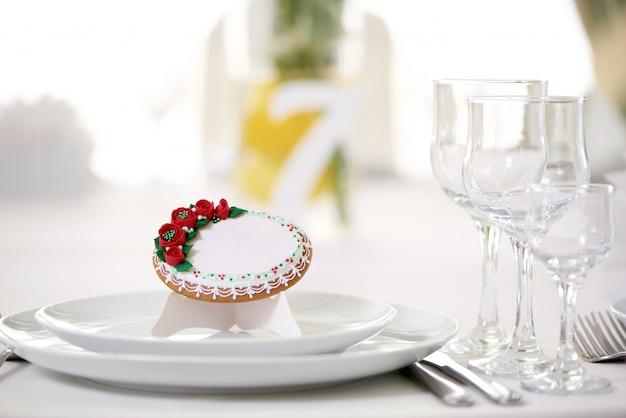 Smaczne piernikowe ciastko pokryte polewą i ozdobione drobnymi czerwonymi różyczkami i wzorem stoi na świątecznym stole weselnym ze szklankami i innymi naczyniami. wygląda pysznie i uroczo.