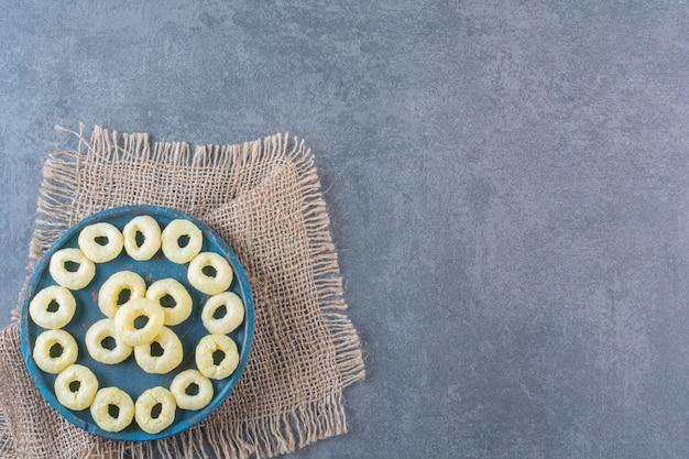 Smaczne pierścienie kukurydziane na drewnianej płycie na fakturze, na marmurowej powierzchni.