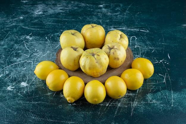 Smaczne pigwy i cytryny na marmurowym stole.