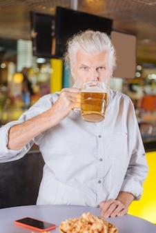 Smaczne piwo. zachwycony wesoły mężczyzna pijący alkohol podczas odpoczynku w pubie
