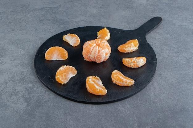 Smaczne plastry mandarynki na desce do krojenia.