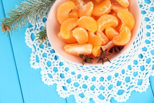 Smaczne plastry mandarynki na kolorowej płytce na niebieskim tle