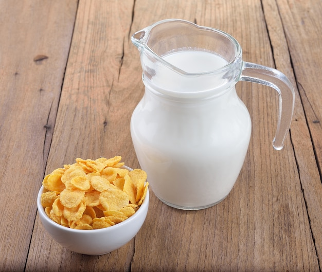 Smaczne płatki kukurydziane w białej misce i szklankę mleka na drewnianym stole