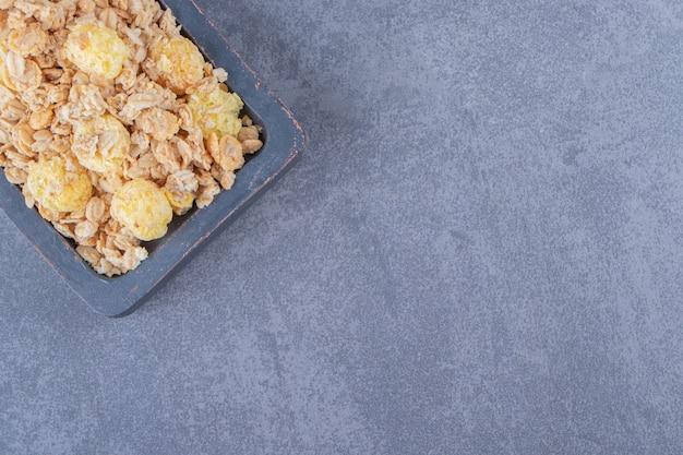 Smaczne płatki kukurydziane w desce, na marmurowym tle. zdjęcie wysokiej jakości