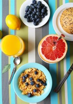 Smaczne płatki kukurydziane z owocami i jagodami na stole z bliska