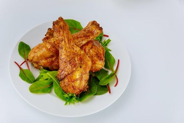 Smaczne podudzia z kurczaka ze szpinakiem na białym talerzu.