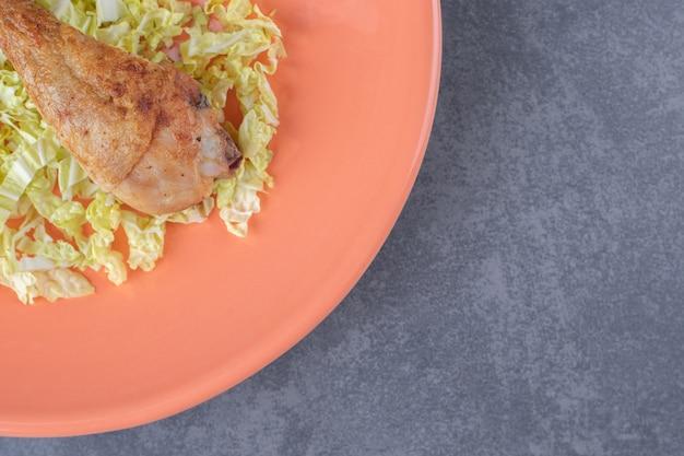 Smaczne podudzie z kurczaka na pomarańczowym talerzu.