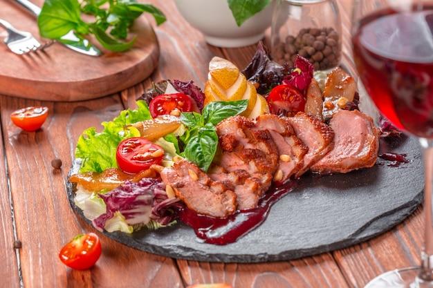 Smaczne pokrojone pieczone piersi kaczki z sałatką ze świeżych warzyw zbliżenie na talerzu.