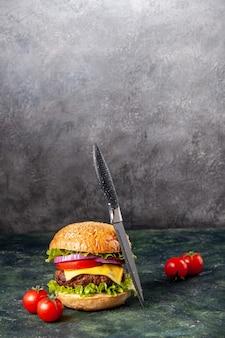 Smaczne pomidory kanapkowe z nożem łodygowym na ciemnej mieszanej powierzchni z wolną przestrzenią