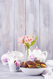 Smaczne profiteroles ze śmietaną na talerzu z herbatą