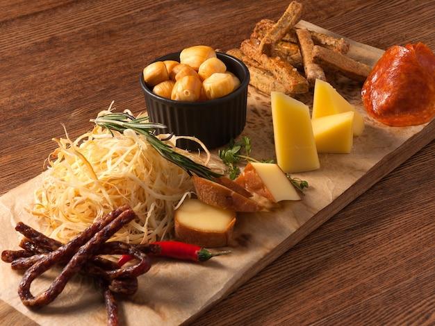 Smaczne przekąski do piwa: różne sery, kiełbaski, salami na drewnianej desce