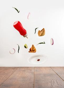 Smaczne przekąski samosa latające z butelką ketchupu, zielonym chilli, plasterkami cebuli i talerzem na prostym tle