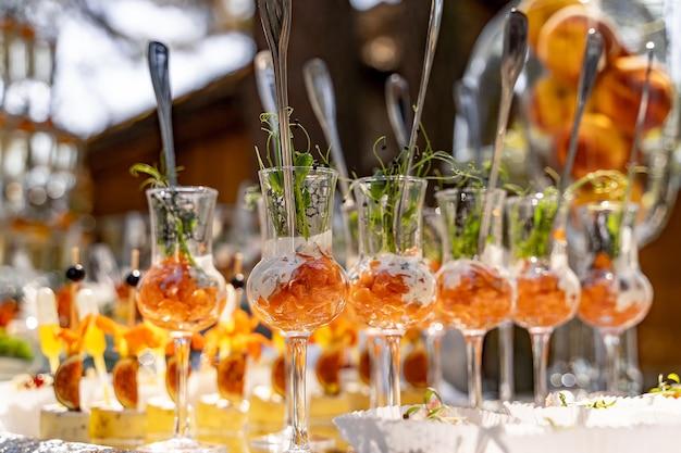 Smaczne przekąski serwowane w szklanych słoikach na drewnianym stole.