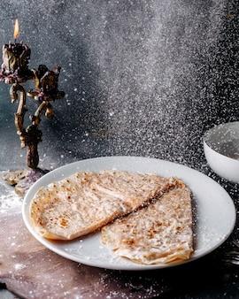 Smaczne qutabs wlewane z mąką do białego talerza na szarej powierzchni